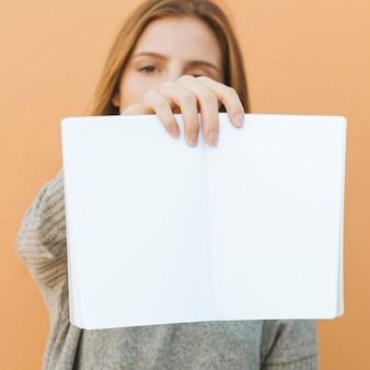 Jeune femme tenant un livre blanc ouvert devant la caméra