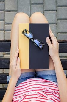 Une jeune femme tenant un livre avec des lunettes noires pour lire dans le parc.