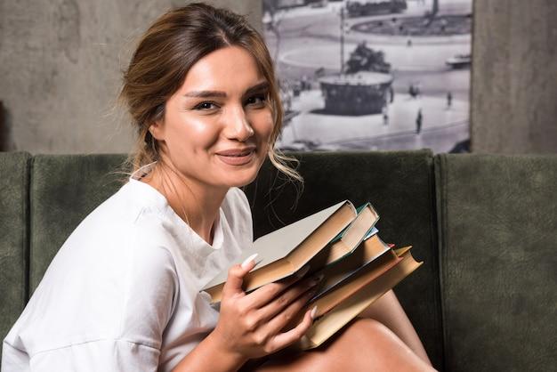Jeune femme tenant des livres sur le canapé avec une expression heureuse.