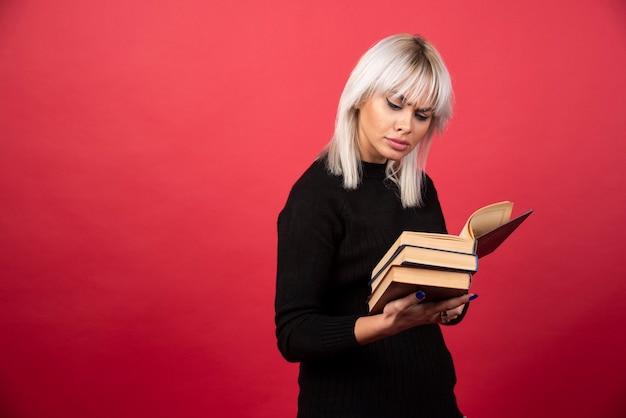 Jeune femme tenant des livres sur un mur rouge.