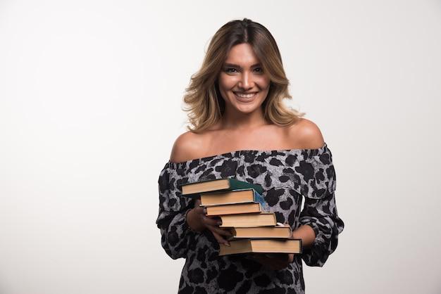 Jeune femme tenant des livres en riant sur un mur blanc.