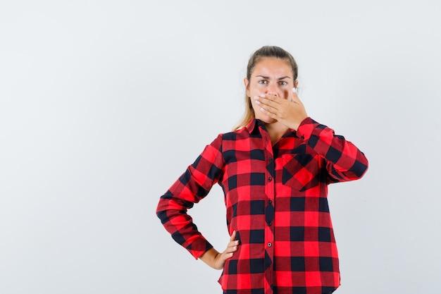 Jeune femme tenant la main sur la bouche en chemise à carreaux et à la surprise