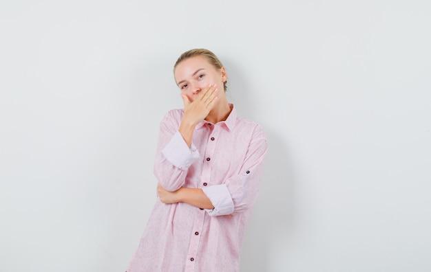 Jeune femme tenant la main sur la bouche en chemise rose et à la surprise