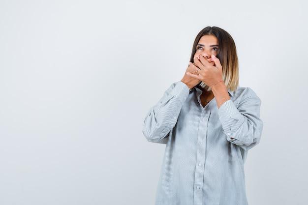Jeune femme tenant la main sur la bouche en chemise surdimensionnée et à la vue de face honteuse.