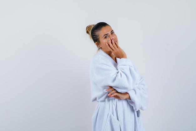 Jeune femme tenant la main sur la bouche en peignoir et à la réflexion