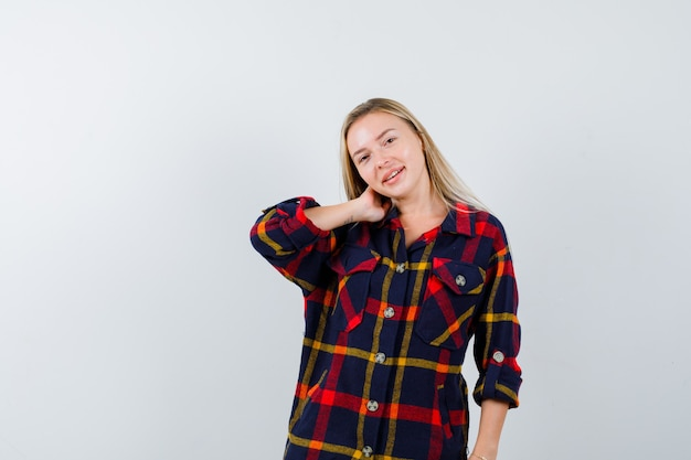 Jeune femme tenant la main sur le cou en chemise à carreaux et à la séduisante, vue de face.