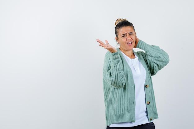 Jeune femme tenant la main sur le cou en t-shirt, veste et semblant anxieuse
