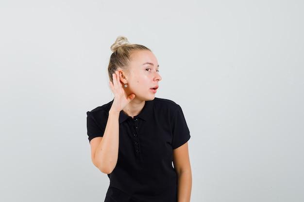 Jeune femme tenant la main derrière l'oreille en t-shirt noir et à la curieuse. vue de face.