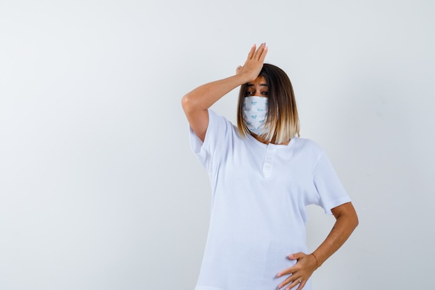 Jeune femme tenant la main sur le front en t-shirt, masque et à la vue oublieuse, de face.