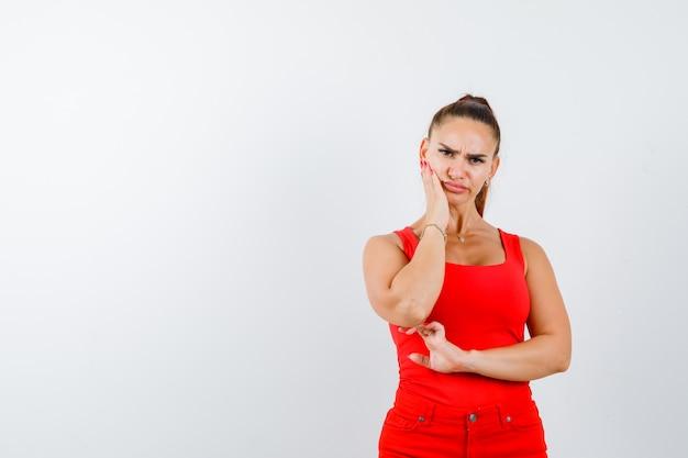 Jeune femme tenant la main sur la joue en maillot rouge, pantalon rouge et à la grave, vue de face.