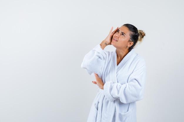 Jeune femme tenant la main sur la joue en peignoir et à la réflexion