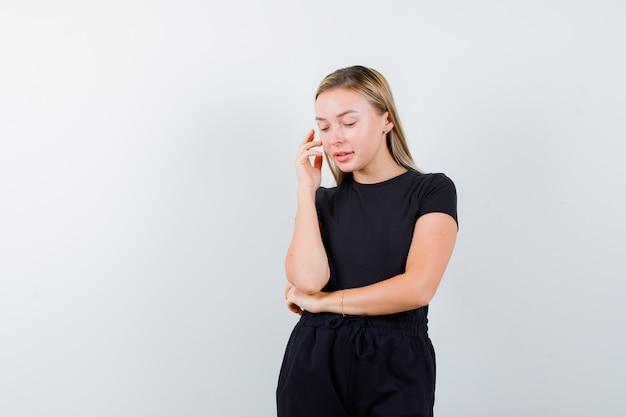 Jeune femme tenant la main sur la joue en t-shirt, pantalon et regardant à travers, vue de face.