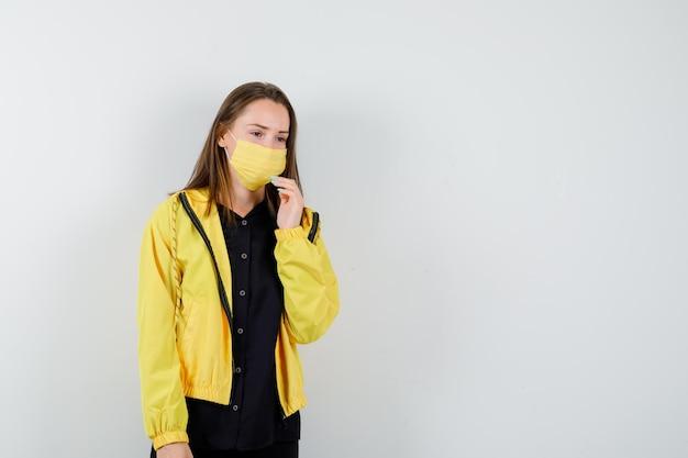 Jeune femme tenant la main sur le menton et pensant à quelque chose