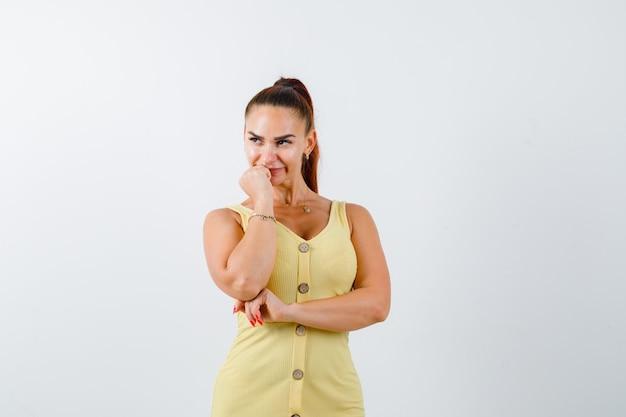 Jeune femme tenant la main sur le menton, à la recherche de suite en robe jaune et à la pensif vue de face.