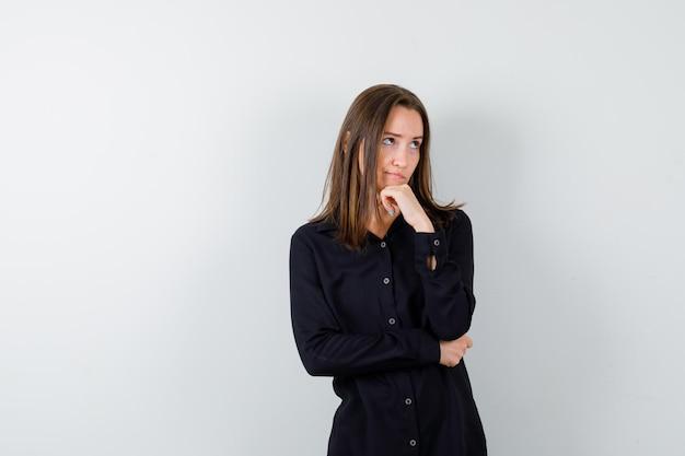 Jeune femme tenant la main sur le menton