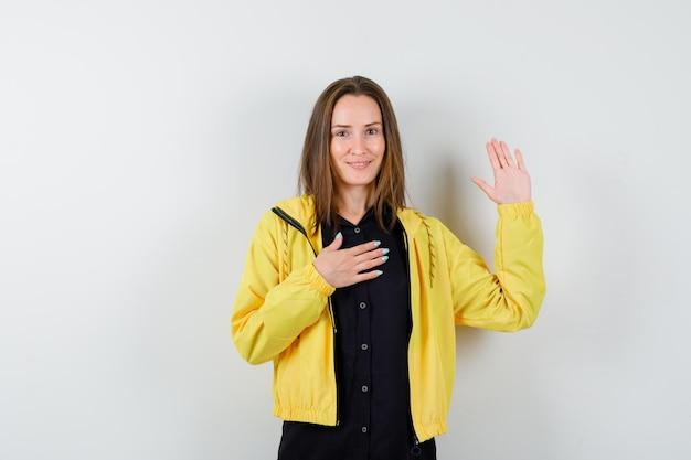 Jeune femme tenant la main sur la poitrine montrant un panneau d'arrêt
