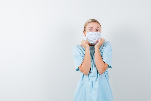 Jeune femme tenant la main près du visage en t-shirt, masque et ayant l'air effrayée isolée