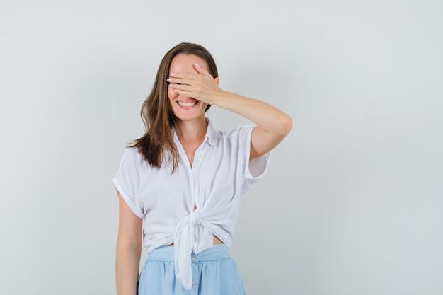 Jeune femme tenant la main sur ses yeux en chemisier et jupe et à la joyeuse