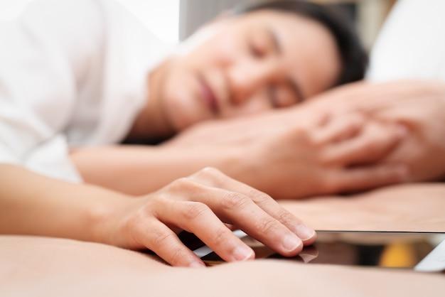 Jeune femme tenant la main sur le smartphone en dormant dans son lit