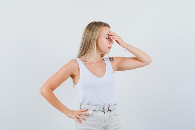 Jeune femme tenant la main sur son front en chemisier blanc et à la recherche d'anxiété