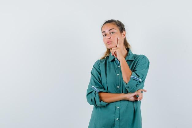 Jeune femme tenant la main sur son visage en chemise bleue et à la réflexion