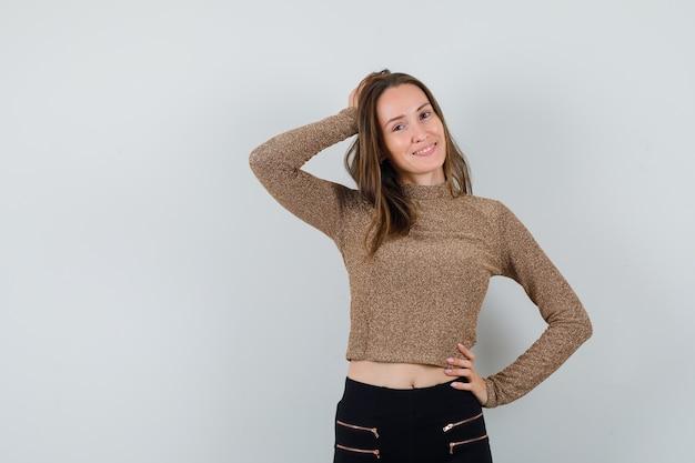 Jeune femme tenant une main sur la taille, une autre main sur la tête en pull doré et pantalon noir et à heureux