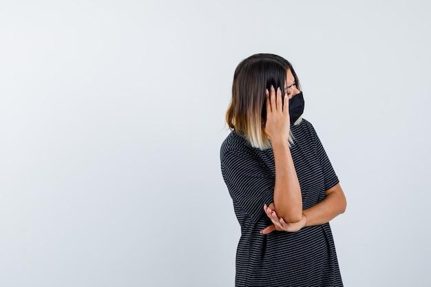 Jeune femme tenant une main sur le temple, une autre main sous le coude en robe noire, masque noir et regardant pensif, vue de face.