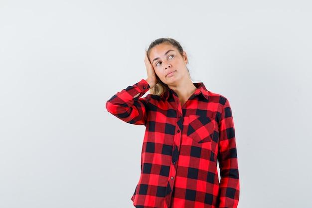 Jeune femme tenant la main sur la tête en chemise à carreaux et à la recherche d'espoir. vue de face.