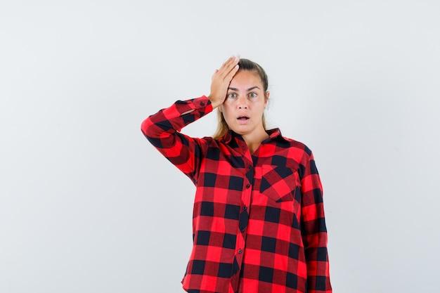Jeune femme tenant la main sur la tête en chemise à carreaux et à la recherche d'oubli