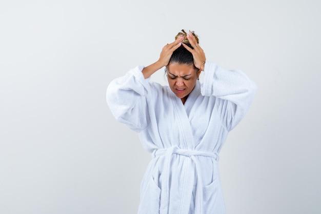 Jeune femme tenant la main sur la tête en peignoir et à l'air ennuyé