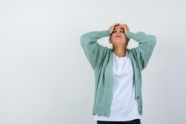 Jeune femme tenant la main sur la tête en t-shirt, veste et l'air ennuyé