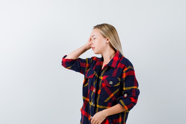 Jeune femme tenant la main sur la tête tout en regardant ailleurs en chemise à carreaux et à la fatigue, vue de face.