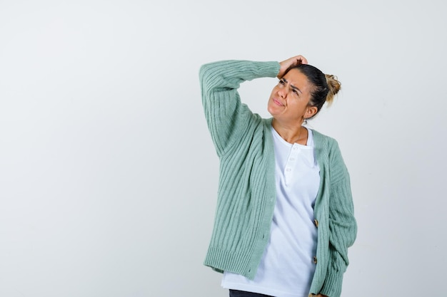 Jeune femme tenant la main sur la tête tout en regardant ailleurs en t-shirt, veste et à la réflexion