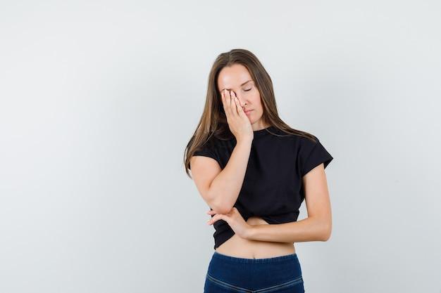 Jeune femme tenant la main sur le visage en chemisier noir, pantalon et à la somnolence