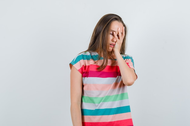 Jeune femme tenant la main sur le visage en t-shirt et à la vue ennuyée, de face.
