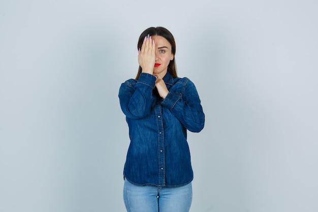 Jeune femme tenant la main sur les yeux en chemise en jean et jeans et à la sérieuse