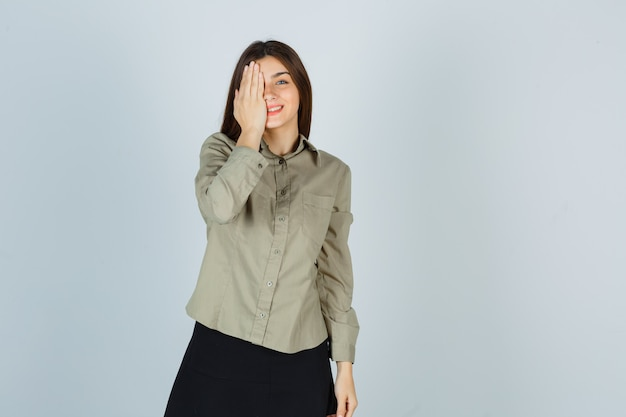 Jeune femme tenant la main sur les yeux en chemise, jupe et à la joyeuse