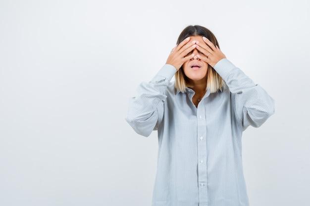 Jeune femme tenant la main sur les yeux en chemise surdimensionnée et l'air fatigué, vue de face.