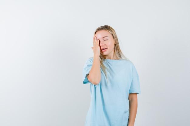 Jeune femme tenant la main sur les yeux en t-shirt et à la recherche de mignon. vue de face.