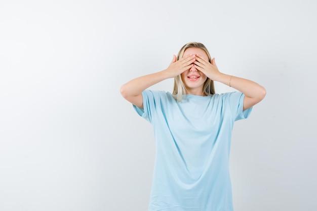 Jeune femme tenant la main sur les yeux en t-shirt et regardant mignon isolé