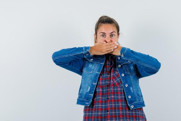Jeune femme tenant les mains sur la bouche en chemise, veste et à la surprise. vue de face.
