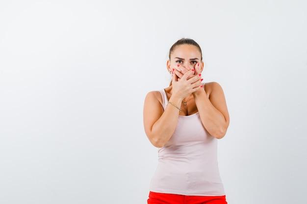 Jeune femme tenant les mains sur la bouche en débardeur beige et à la peur, vue de face.