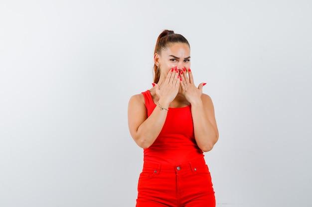 Jeune femme tenant les mains sur la bouche en maillot rouge, pantalon rouge et regardant cendré, vue de face.
