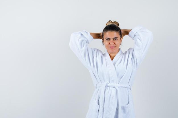 Jeune femme tenant les mains derrière la tête en peignoir et à la confiance