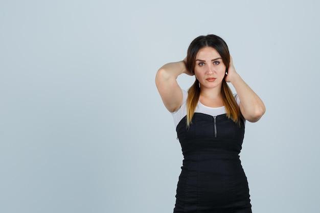 Jeune femme, tenant mains, derrière, tête
