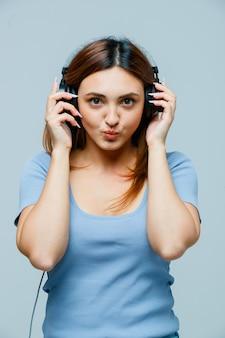 Jeune femme tenant les mains sur les écouteurs tout en boudant les lèvres
