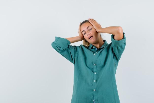 Jeune femme, tenant mains, sur, elle, tête, dans, chemise bleue, et, regarder, anxieux