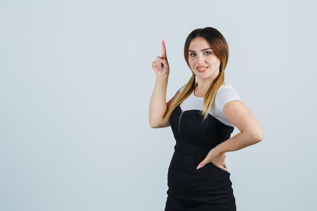 Jeune femme tenant les mains sur la hanche et pointant l'index dans le geste eurêka
