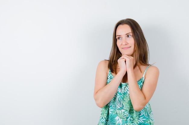 Jeune femme tenant les mains jointes sous le menton en blouse et l'air mignon. vue de face.