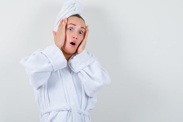 Jeune femme tenant les mains sur les joues en peignoir blanc, serviette et à la peur, vue de face.